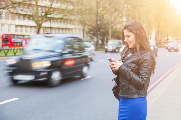 Jovem, mulher, digitando em seu telefone inteligente por uma estrada movimentada em londres Foto Premium