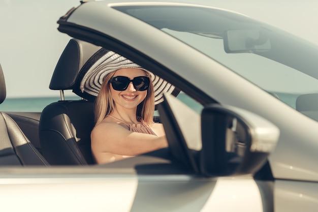 Jovem mulher dirige um carro na praia Foto Premium