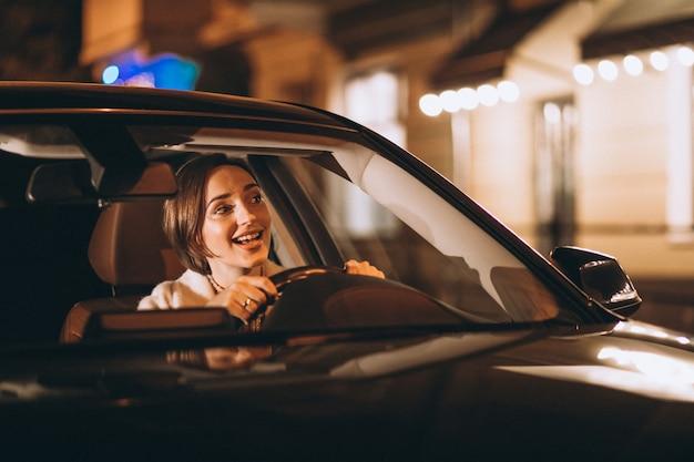 Jovem mulher dirigindo carro à noite Foto gratuita