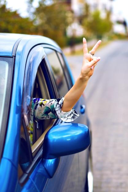 Jovem mulher dirigindo carro no campo, colocar a mão fora do carro desfrutar de sua liberdade, fazendo boa ciência yo por sua mão, conceito de férias de viagem. Foto gratuita