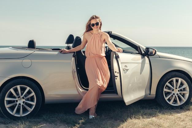 Jovem mulher dirigir um carro na praia Foto Premium