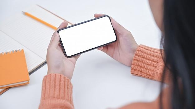 Jovem mulher do close-up que guarda o smartphone com tela isolada. Foto Premium
