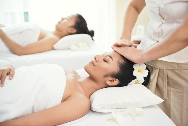 Jovem mulher dois bonita que começ o salão de beleza da massagem dos termas e a flor branca em sua orelha. Foto Premium