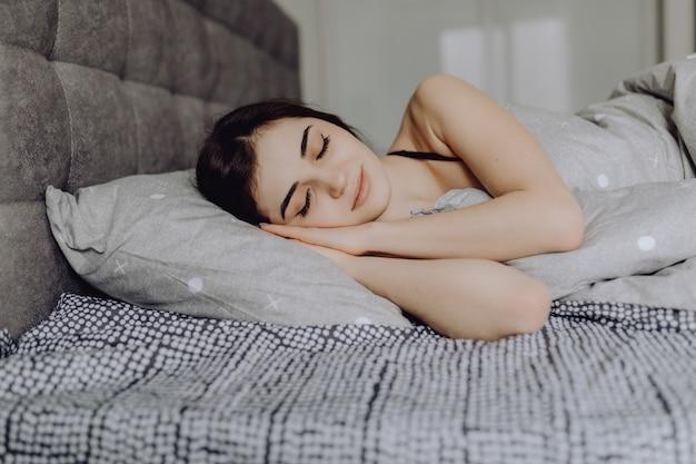 Jovem mulher dormindo. bela jovem sorridente, dormindo na cama Foto gratuita