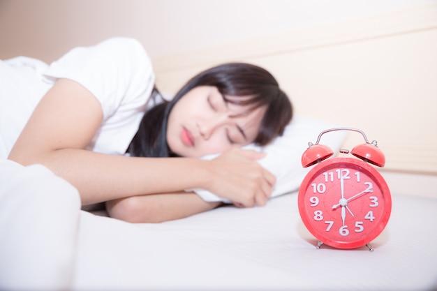 Jovem mulher dormindo e despertador no quarto em casa Foto gratuita