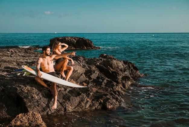 Jovem mulher e homem apontando para o lado com pranchas de surf na rocha perto do mar Foto gratuita