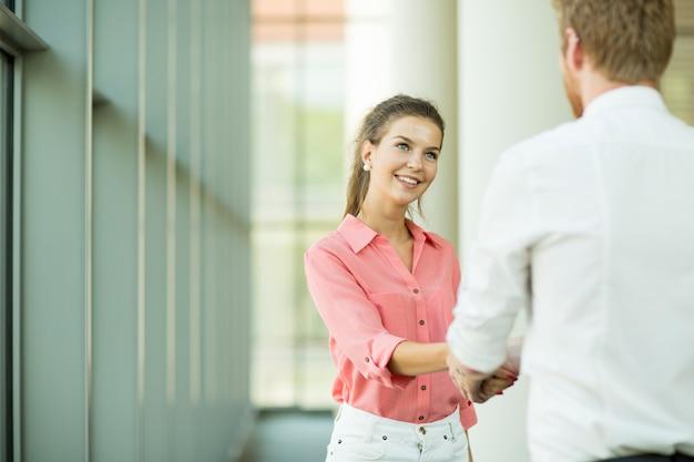 Jovem mulher e homem handshaking Foto Premium