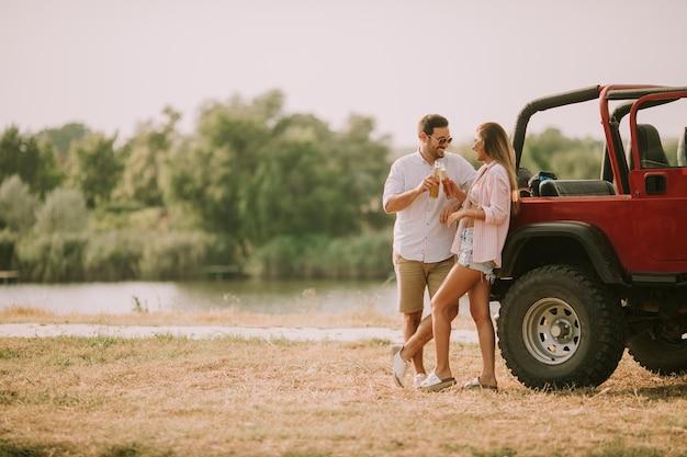 Jovem mulher e homem se divertindo ao ar livre perto de carro Foto Premium