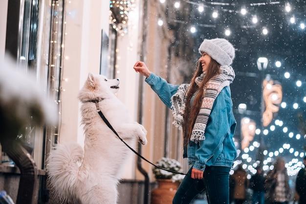 Jovem mulher e um cachorro branco que mostra truques em uma rua Foto gratuita