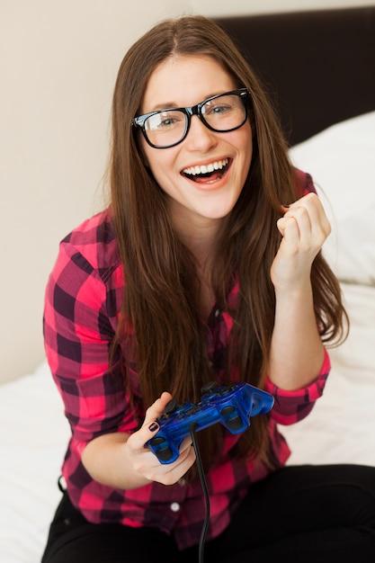 Jovem mulher em casual jogando videogame Foto gratuita