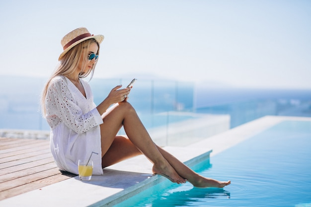 Jovem mulher em férias na piscina usando telefone Foto gratuita