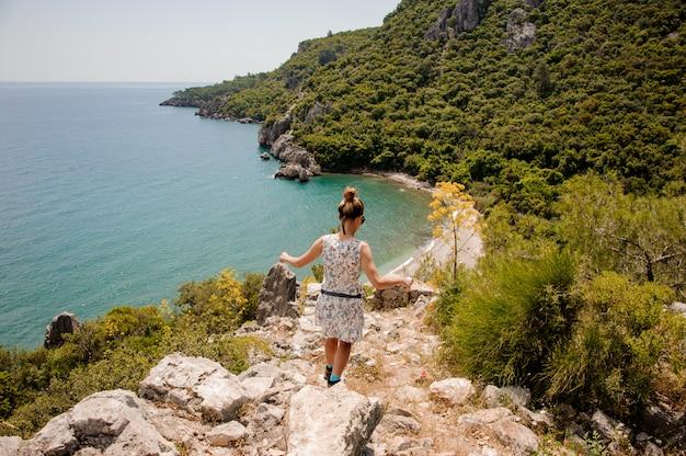 Jovem mulher em pé de vestido na montanha Foto Premium
