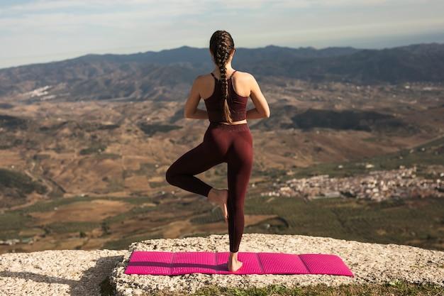 Jovem mulher em pose de ioga com as costas Foto gratuita
