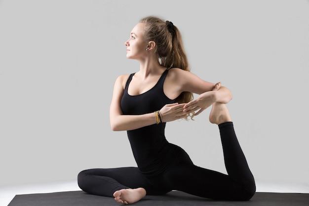 Jovem mulher em pose de pombo-rei com uma perna, estúdio cinza Foto gratuita