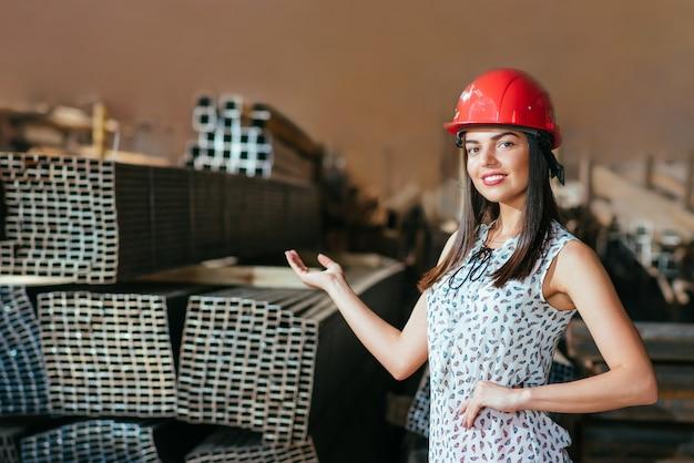 Jovem mulher em um armazém com um capacete de segurança Foto Premium