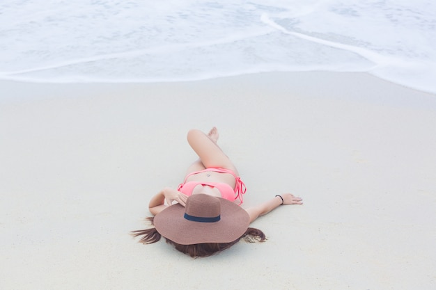 Jovem mulher em um biquini que encontra-se na praia e nas ondas da areia, jovem mulher que toma sol e que relaxa no sandy beach branco, conceito do curso do verão. Foto Premium