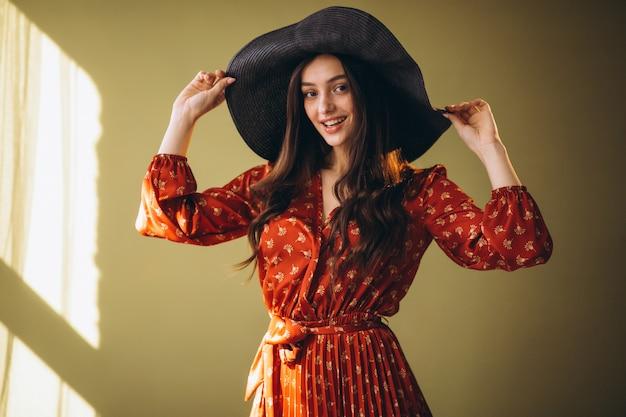 Jovem mulher em um lindo vestido e chapéu Foto gratuita