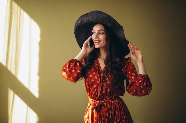 Jovem mulher em um lindo vestido usando telefone e compras on-line Foto gratuita