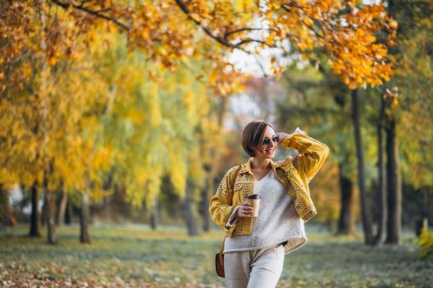Jovem mulher em um parque outono bebendo café Foto gratuita