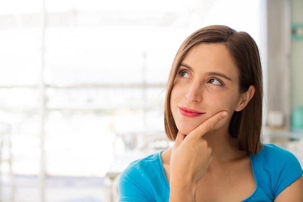 Jovem mulher em um pensamento de restaurante Foto Premium