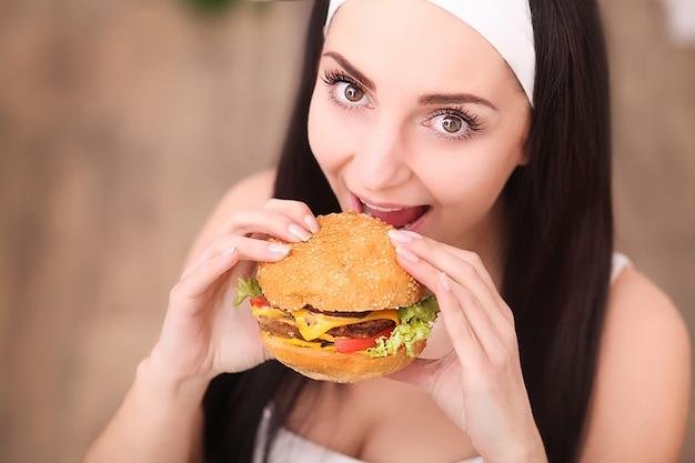 Jovem mulher em um restaurante fino comer um hambúrguer, ela se comporta indevidamente Foto Premium