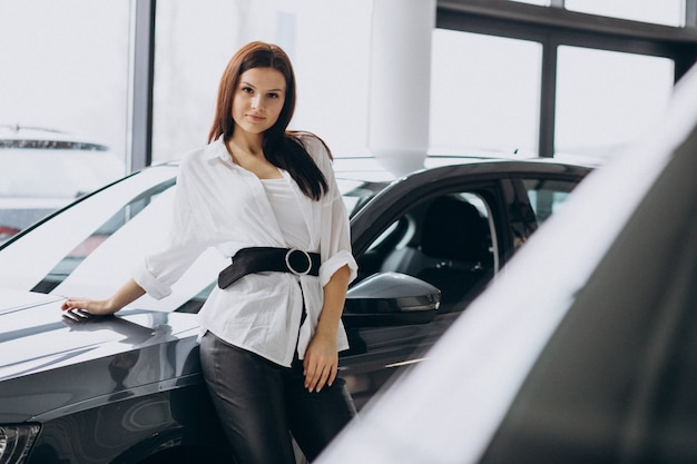 Jovem mulher em um showroom de carro, escolhendo um carro Foto gratuita