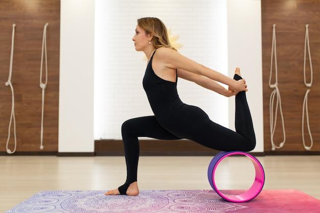Jovem mulher em um sportswear yoga exercícios com uma roda de ioga no ginásio. estilo de vida de alongamento e bem-estar Foto Premium