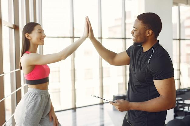 Jovem mulher em um top rosa em pé com um treinador Foto gratuita