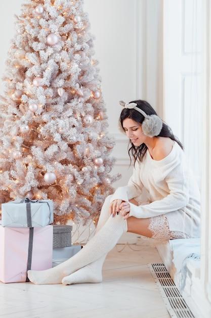 Jovem mulher em um vestido elegante perto da árvore de natal Foto gratuita