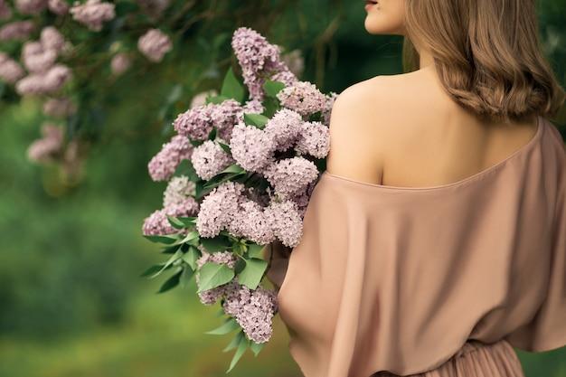 Jovem mulher em um vestido está de pé perto de um arbusto lilás Foto Premium