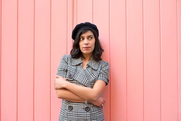 Jovem mulher em um vestido xadrez preto e branco, olhando para a direita em uma parede rosa. Foto Premium