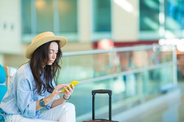 Jovem mulher em uma aeronave de espera do vôo da sala de estar do aeroporto. Foto Premium