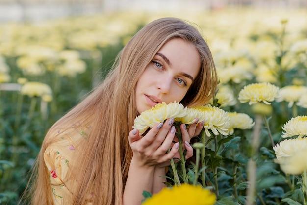 Jovem mulher em uma estufa com flores Foto gratuita