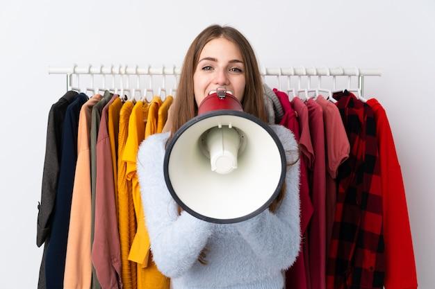 Jovem mulher em uma loja de roupas, segurando um megafone Foto Premium