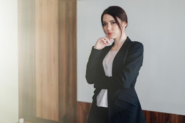 Jovem mulher emocional atraente em roupas de estilo empresarial Foto Premium