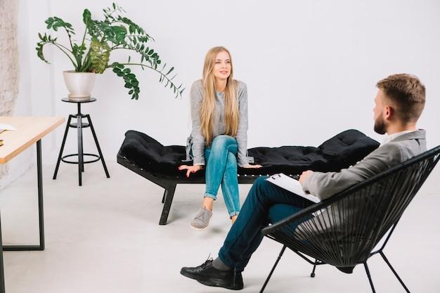 Jovem mulher emocionalmente falando e discutindo com o psicoterapeuta seus problemas Foto gratuita