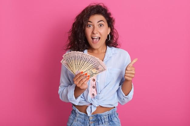 Jovem mulher encaracolada caucasiana segurando o monte de notas posando isolado sobre parede rosa, ser feliz e surpreso, fica com um grande sorriso, aparecendo o polegar com os dedos, Foto Premium