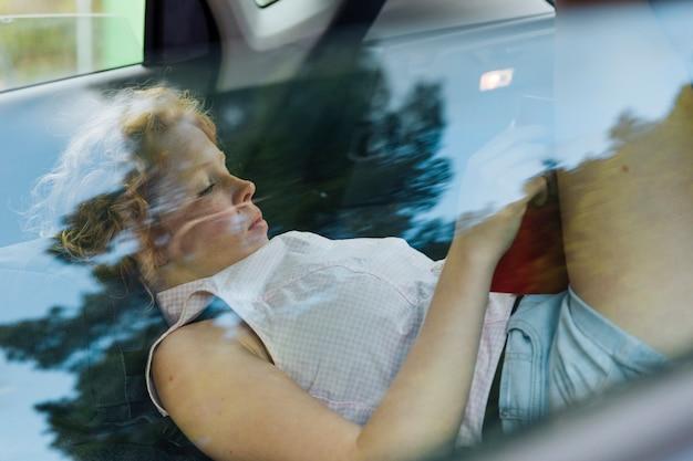 Jovem mulher encaracolada descansando enquanto estava deitado no carro Foto gratuita