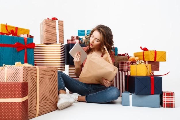 Jovem mulher encaracolada, sentada no chão entre caixas de presente, abrindo presentes Foto gratuita