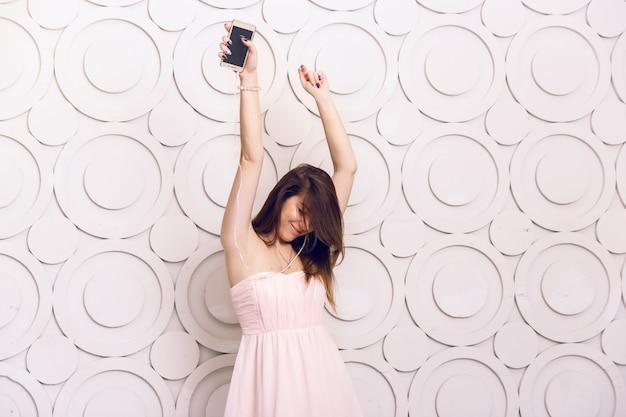 Jovem mulher enérgica dançando ouvindo música em fones de ouvido Foto Premium