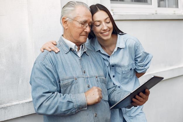 Jovem mulher ensinando seu avô como usar um tablet Foto gratuita