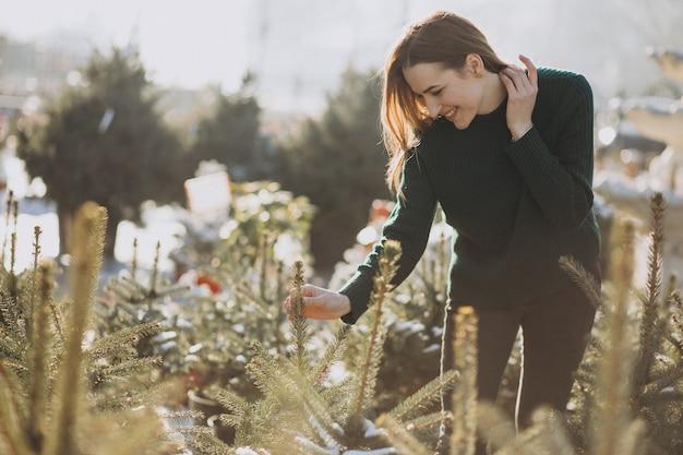 Jovem mulher escolhendo uma árvore de natal em uma estufa Foto gratuita