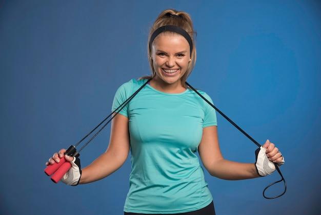 Jovem mulher esportiva pendurando cordas de pular em seu pescoço e sorrindo. Foto gratuita