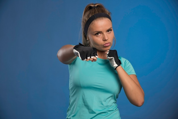 Jovem mulher esportiva segurando os punhos e boxe. Foto gratuita