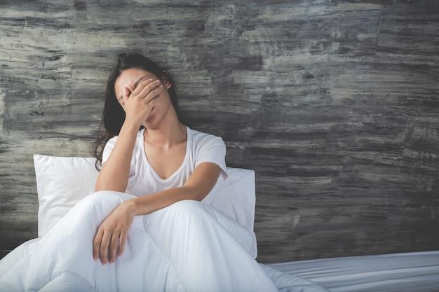Jovem mulher está deprimida em uma cama branca Foto gratuita