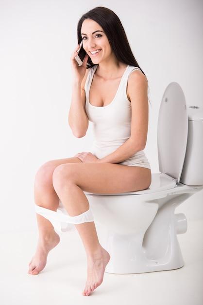 Jovem mulher está falando por telefone enquanto está sentado no banheiro. Foto Premium