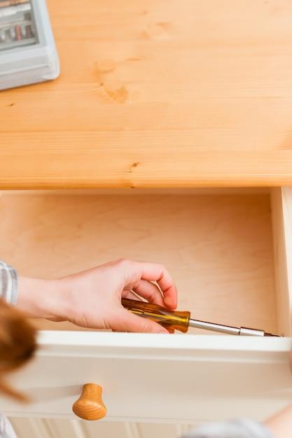 Jovem mulher está montando um armário Foto Premium