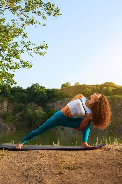 Jovem mulher está praticando ioga perto do rio Foto gratuita