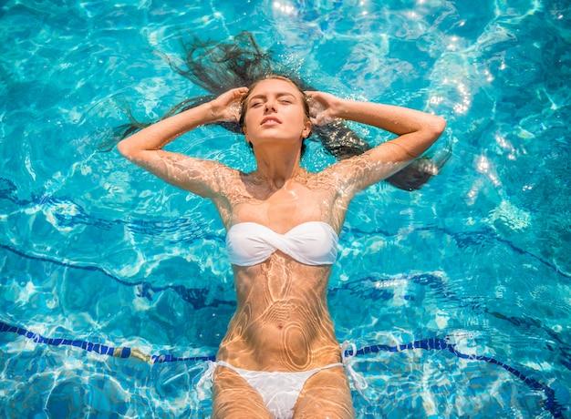Jovem mulher está relaxando na piscina. Foto Premium