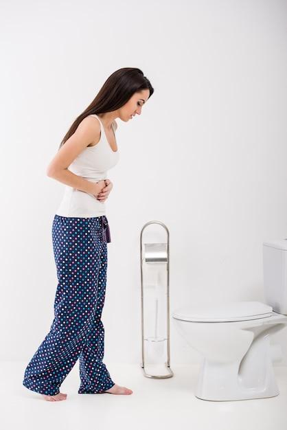 Jovem mulher está se sentindo mal no banheiro. Foto Premium